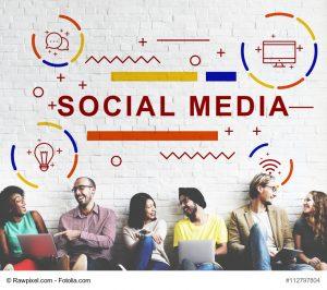 Menschen sitzen auf einer Bank und reden mit Laptops auf dem Schoß, darüber der Schriftzug Social Media