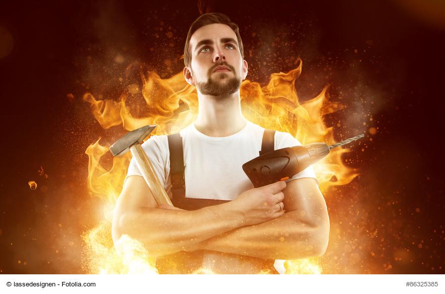 Ein Handwerker steht wie ein Held im Feuerschein mit gekreuzten Armen, Hammer und Bohrmaschine als Sinnbild für Heldengeschichten.