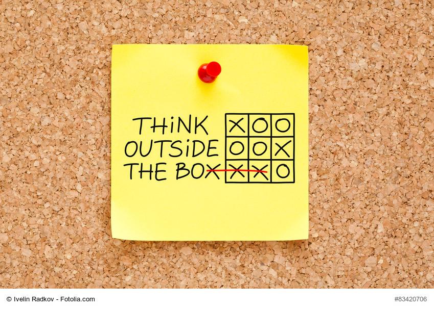 """Ein gelber Post-it auf einer Pinnwand aus Kork mit dem Spruch """"Think outside the box"""" und tic-tac-toe Spiel"""