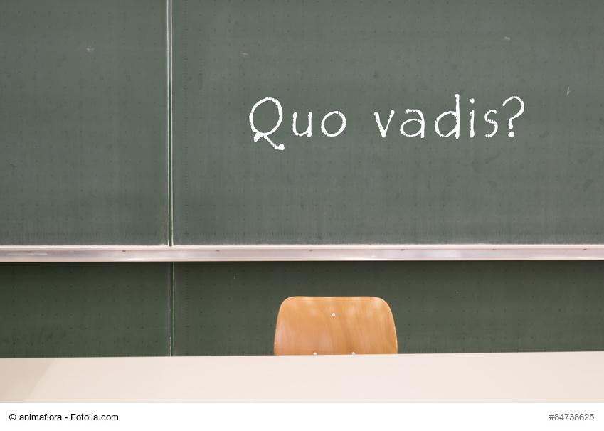 """Schultafel hinter einem Lehrertisch mit Stuhl auf der """"Quo vadis"""" steht"""