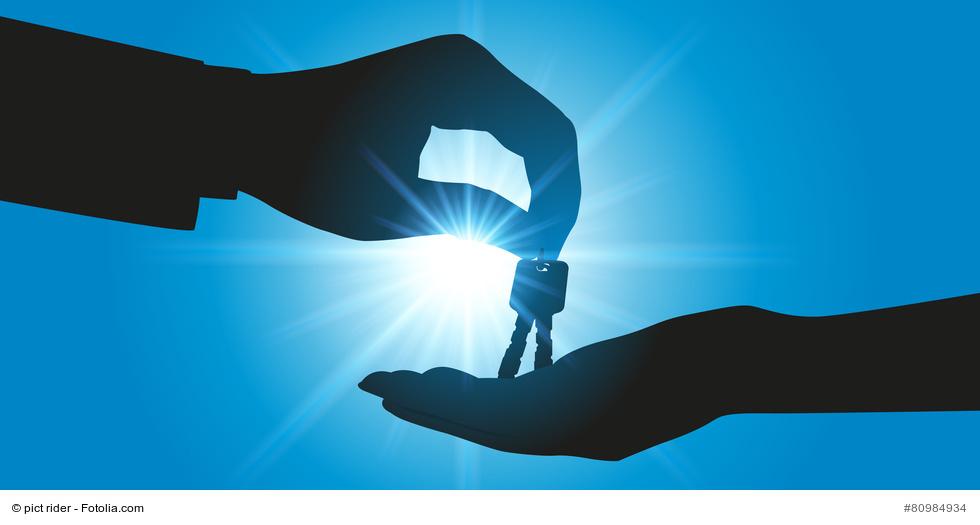 Zwei Hände übergeben einen Schlüsselbund vor dem strahlenden Licht der Sonne an blauem Himmel