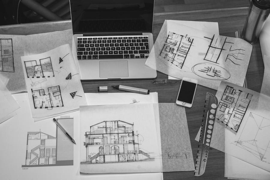 Skizzen und Grundrisse liegen verstreut um ein Laptop und ein Smartphone herum.