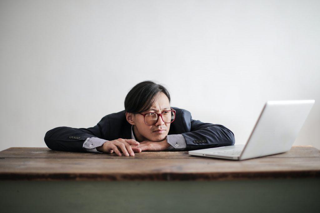 Ein Mann sitzt demotiviert vor dem Laptop