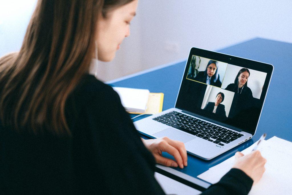 eine Person sitzt vor dem Laptop in einer Videokonferenz